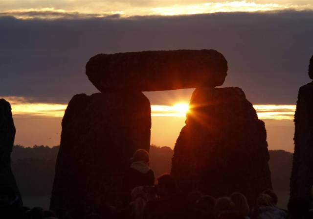 The sun rises behind the Stonehenge monument in England, during the summer solstice shortly after 04.52 am, Monday, June 21.